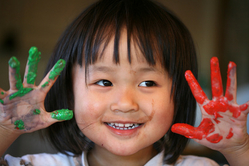 kindergartner with paint on hands
